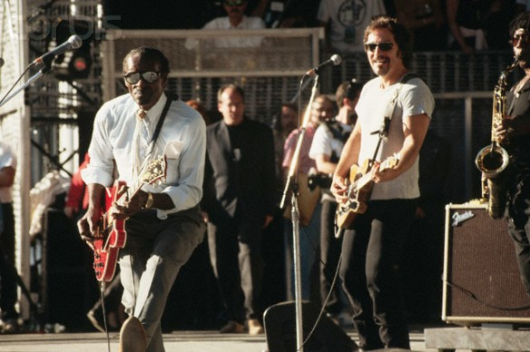 Chuck Berry duck walks with a smiling Bruce Springsteen watching. Rehearsal for September 1995 Rock and Roll Hall of Fame concert